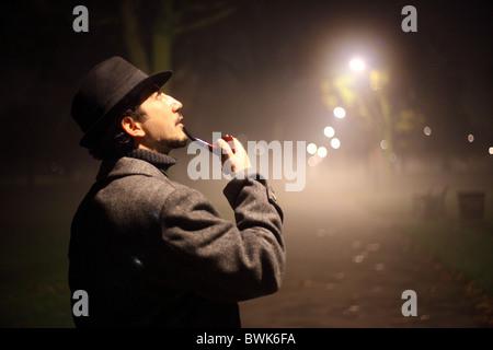 man smoking pipe in the dark