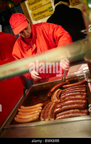 woman cooking sausages Christmas market Vienna - Stock Photo