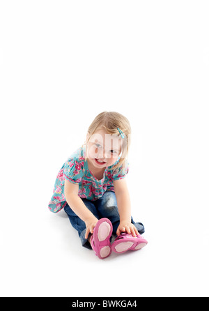 toddler sitting on floor with isolated white background - Stock Photo