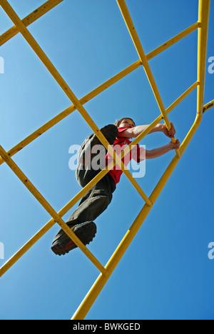 boy child boy Seven-year-old climbing scaffolding climbing scaffolding sky children playground playground pl - Stock Photo