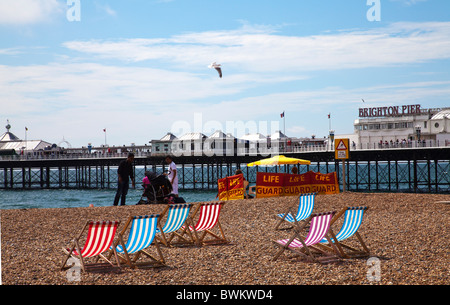 Lifeguards and holidaymakers an deckchairs on beach with a view towards Brighton Pier - Stock Photo