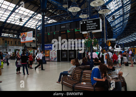 Travellers commuters waiting for trains at Brighton Railway Station - Stock Photo