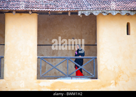 Muslim woman on a mobile phone in Lamu Fort or Fumo Madi ibn Abi Bakr, Lamu Island, Kenya - Stock Photo