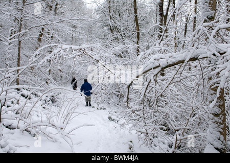 People walking through snow laden trees in a snowy landscape - Stock Photo