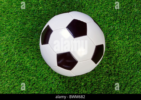 A white and black chequered leather football or soccer ball on grass. - Stock Photo