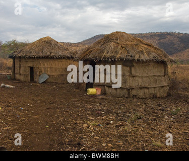 Traditional Masai mud and thatch huts in Tanzania. - Stock Photo
