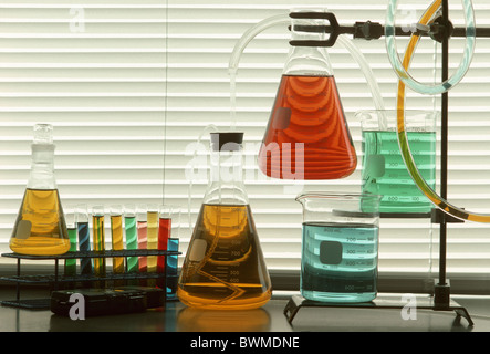 Scientific glassware and tubes filled with colored liquids against window blinds - Stock Photo