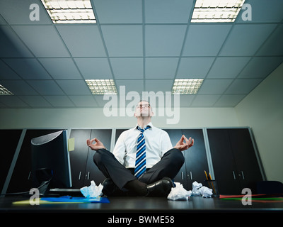 Mature businessman sitting on desk in lotus position. Horizontal shape, full length, Copy space - Stock Photo