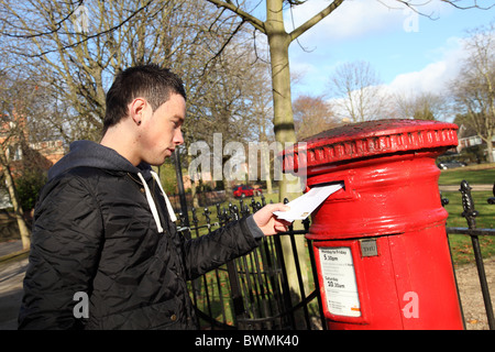 A young man posting letters in a U.K. city. - Stock Photo