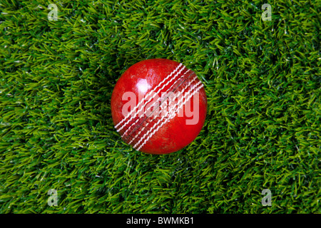 Photo of a red leather cricket ball with stitched seams on grass - Stock Photo
