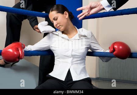 Portrait of tired businesswoman in boxing gloves sleeping on boxing ring after hard game - Stock Photo