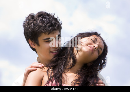 Photo of handsome man embracing tenderly beautiful woman on background of sky - Stock Photo