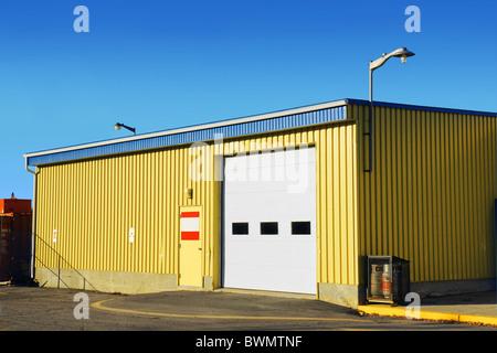 small corrugated yellow metal siding garage or arena - Stock Photo