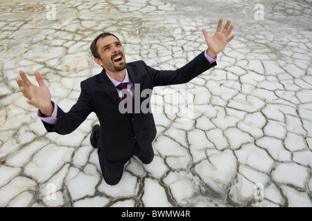 Photo of helpless businessman standing on dry ground and raising his arms upwards - Stock Photo
