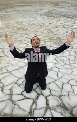 Photo of helpless businessman standing on dry ground and screaming with raised arms - Stock Photo