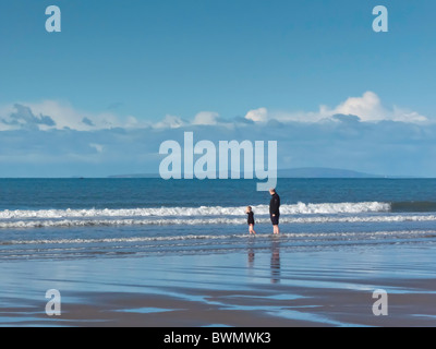 Father and small son paddling together in sea, on shoreline with sandy beach and calm sea, blue sky with distant - Stock Photo