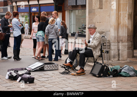Street busker playing a guitar to collect money by old market cross in city centre in Chichester, West Sussex, England, - Stock Photo
