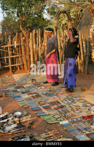 Zulu Women Selling Souvenirs to Tourist Guests, Shakaland Zulu Village, Nkwalini Valley, Kwazulu Natal, South Africa. - Stock Photo