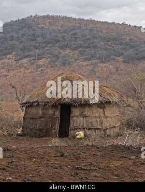 Traditional Masai mud and thatch hut in Tanzania. - Stock Photo