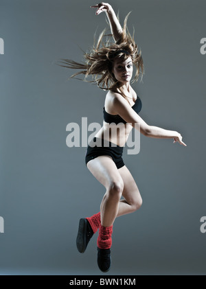 beautiful young caucasian woman girl dancer ballet breakdance leap jump on studio isolated background - Stock Photo