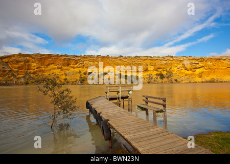 Afternoon light on golden cliffs and an old jetty on the Murray River at Walker Flat - Stock Photo