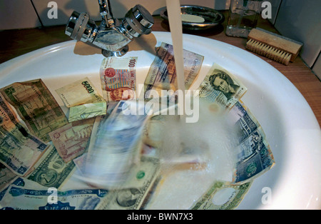 Washing international banknotes in a bathroom sink. - Stock Photo