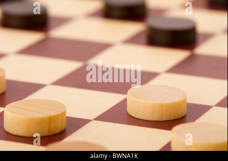 Playing checkers with wooden black and white pawns - Stock Photo