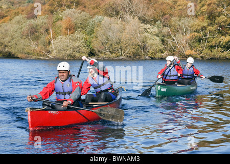 People canoeing in Canadian canoes on Llyn Padarn Lake in Snowdonia National Park. Llanberis, Gwynedd, North Wales, - Stock Photo