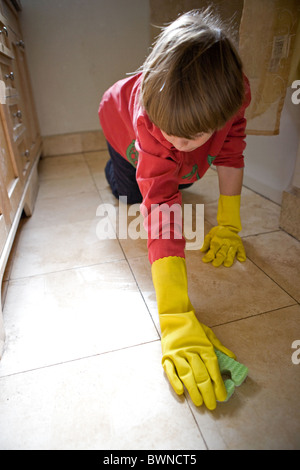 Eight year old boy scrubbing tile on bathroom floor wearing latex gloves, weekly household chore, United States. - Stock Photo