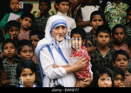 Mother Teresa accompanied by children at her mission in Calcutta, India - Stock Photo