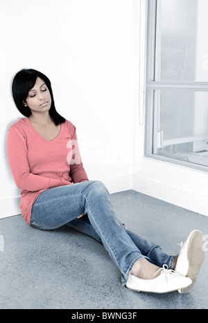 Tired black woman sitting against wall with eyes closed - Stock Photo