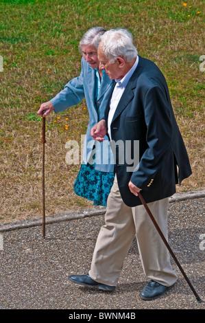 Mature / middle-aged couple walking along pavement - France. - Stock Photo