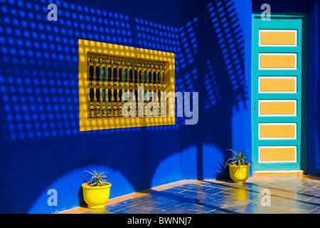 Yellow pots and window in a blue wall at jardin majorelle marrakech stock photo