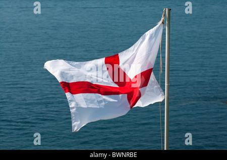 Cross of Saint George flag, national flag of England, with sea beyond - Stock Photo