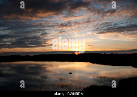 Reflections of sunset and clouds in water of pond on Dartmoor, Devon UK - Stock Photo
