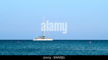 White yacht in blue sea on horizon in Mediterranean sea - Stock Photo