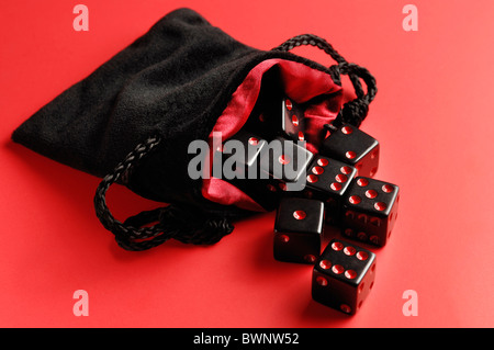 Set of black dice in a pouch isolated on red background - Stock Photo