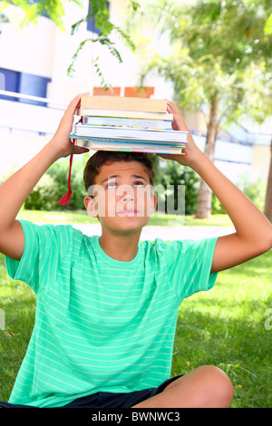 boy teenager student holding head stacked books heavy weight - Stock Photo