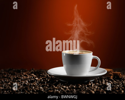 Christmas tree shaped steam rising over a cup of coffe latte standing on coffee beans isolated on dark red background - Stock Photo