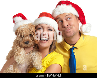 Portrait of a happy young man and a woman with a Cockapoo dog in her hands wearing red Christmas hats. - Stock Photo