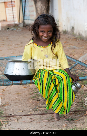Happy young poor lower caste Indian street girl smiling, sitting on a bed in the street. Andhra Pradesh, India - Stock Photo