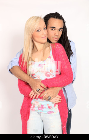 Blond girl and boy with dreadlocks cuddling - Stock Photo