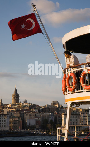TURKEY Istanbul Sultanahmet Passenger ferry with Turkish flag. Man leaning on railings of upper deck with Galata - Stock Photo