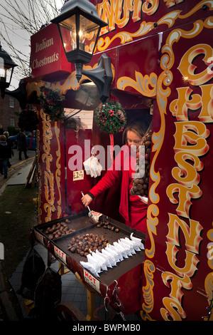 hot roasted chestnut seller in christmas market - Stock Photo