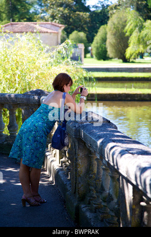 An attractive woman leaning on a balustrade and taking a photograph over the River Dronne at Brantome Dordogne France - Stock Photo