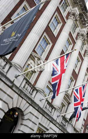 Low level and up looking angled aspect of the flags above the rear main entrance to the Millennium Hotel in Grosvenor - Stock Photo
