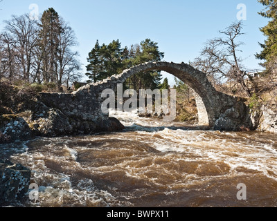Old Packhorse Bridge over  Dulnain river in spate with melt waters, winter,  Carrbridge, near Aviemore, Cairngorms, - Stock Photo