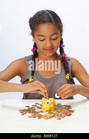 A girl with her savings and a piggy bank - Stock Photo
