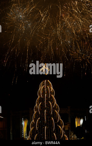 Fireworks explode over a public Christmas tree in Vilnius, Lithuania. - Stock Photo