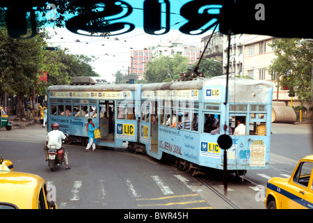 One of Kolkata's elderly trams viewed from inside a city bus - Stock Photo